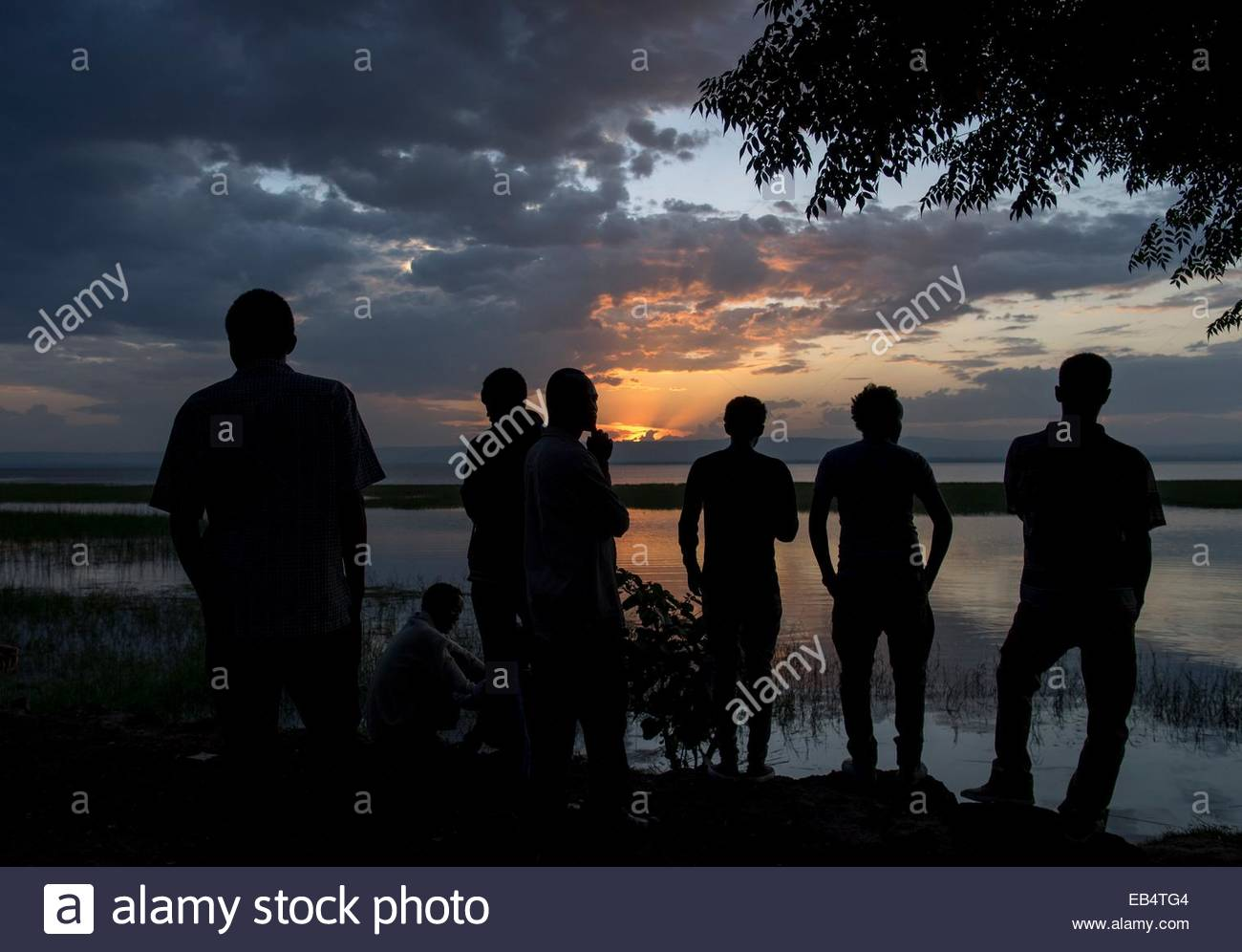 Men silhouetted against Lake Awasa at sunset. - Stock Image