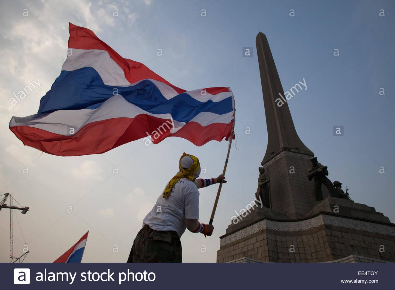A protestor waves a flag at a rally in Victory Square, Bangkok. - Stock Image