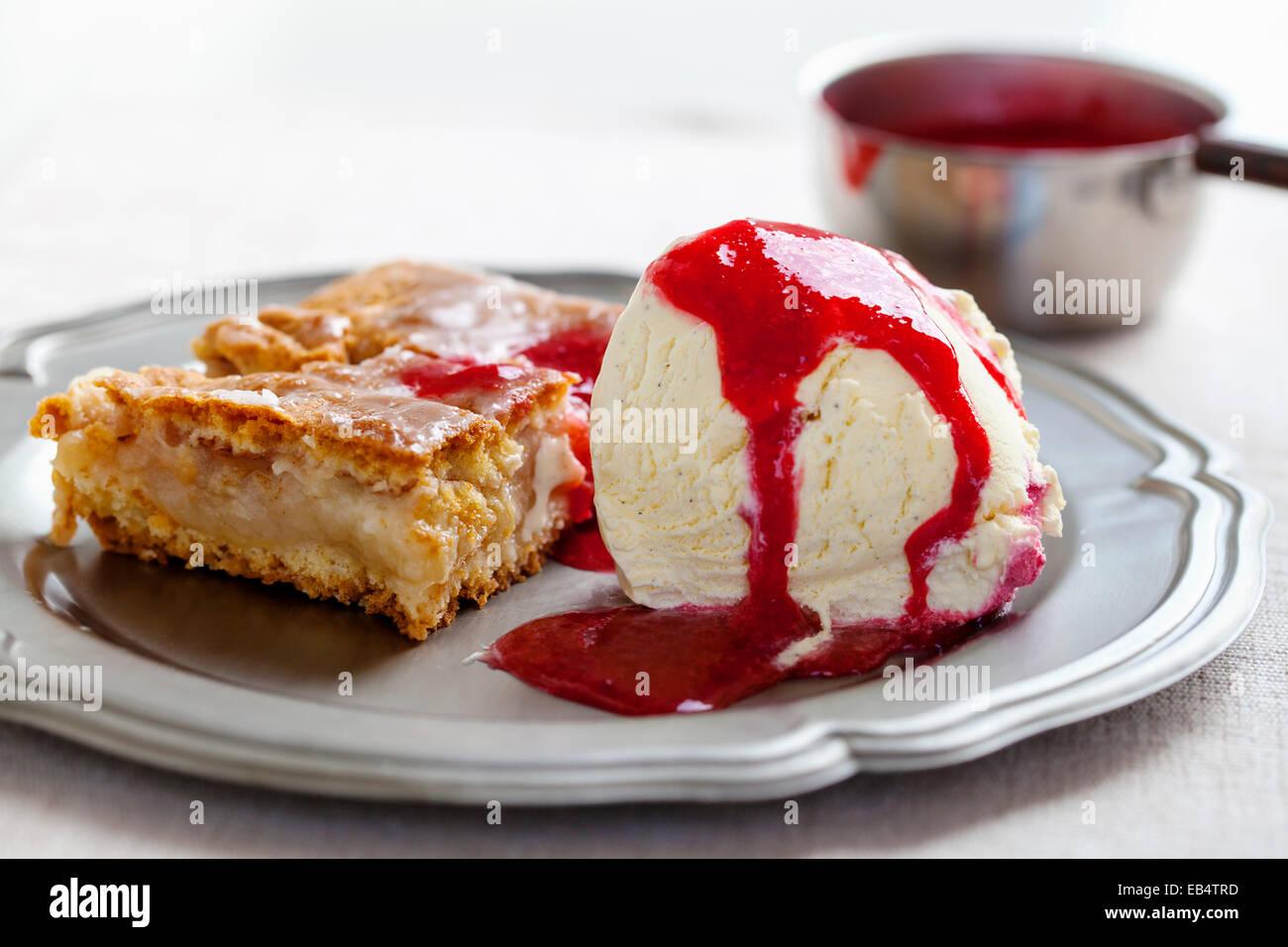 Apple cake with vanilla ice cream and raspberry sauce - Stock Image