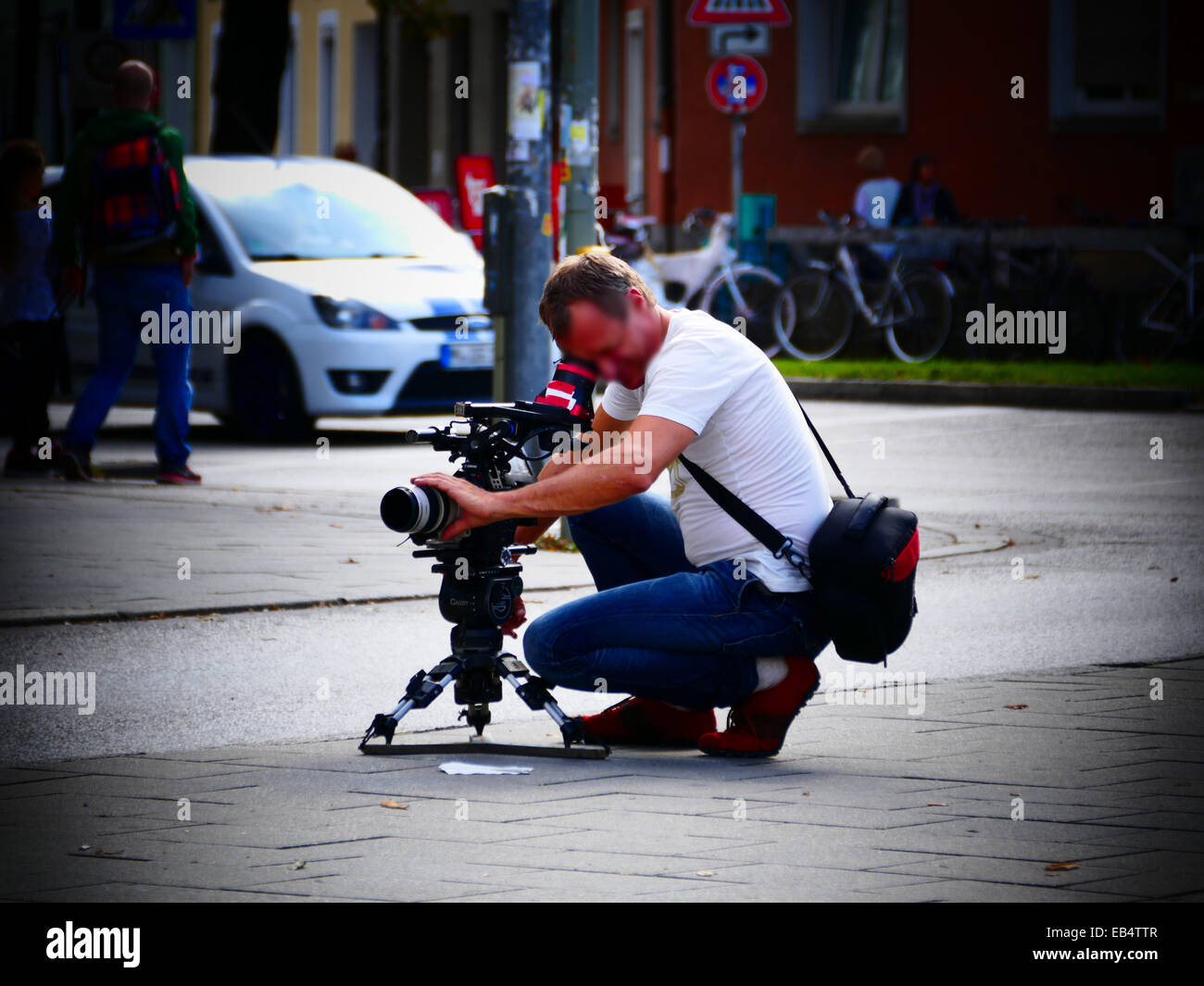 Cameraman shooting filming in the street - Stock Image