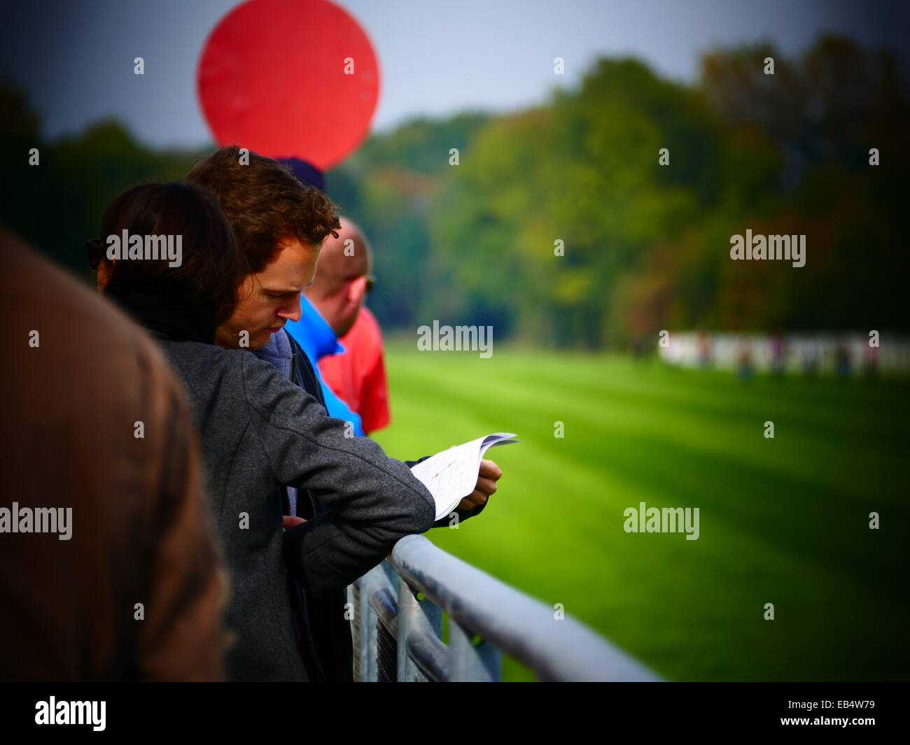 People at Track studying racing program Horse Race Racing - Stock Image