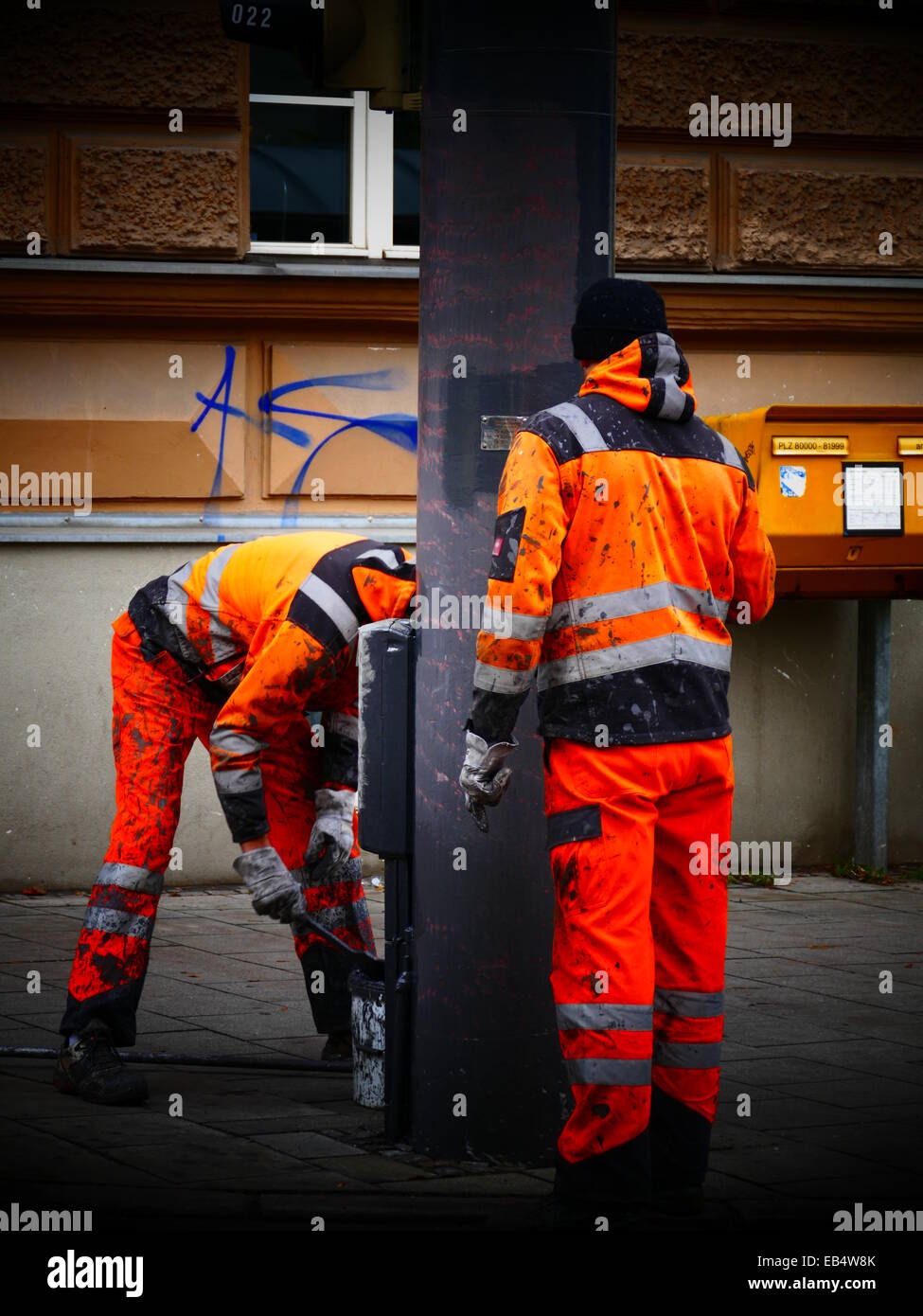 Communal Workers with reflective orange Workwear Jacket painting Traffic Pole - Stock Image