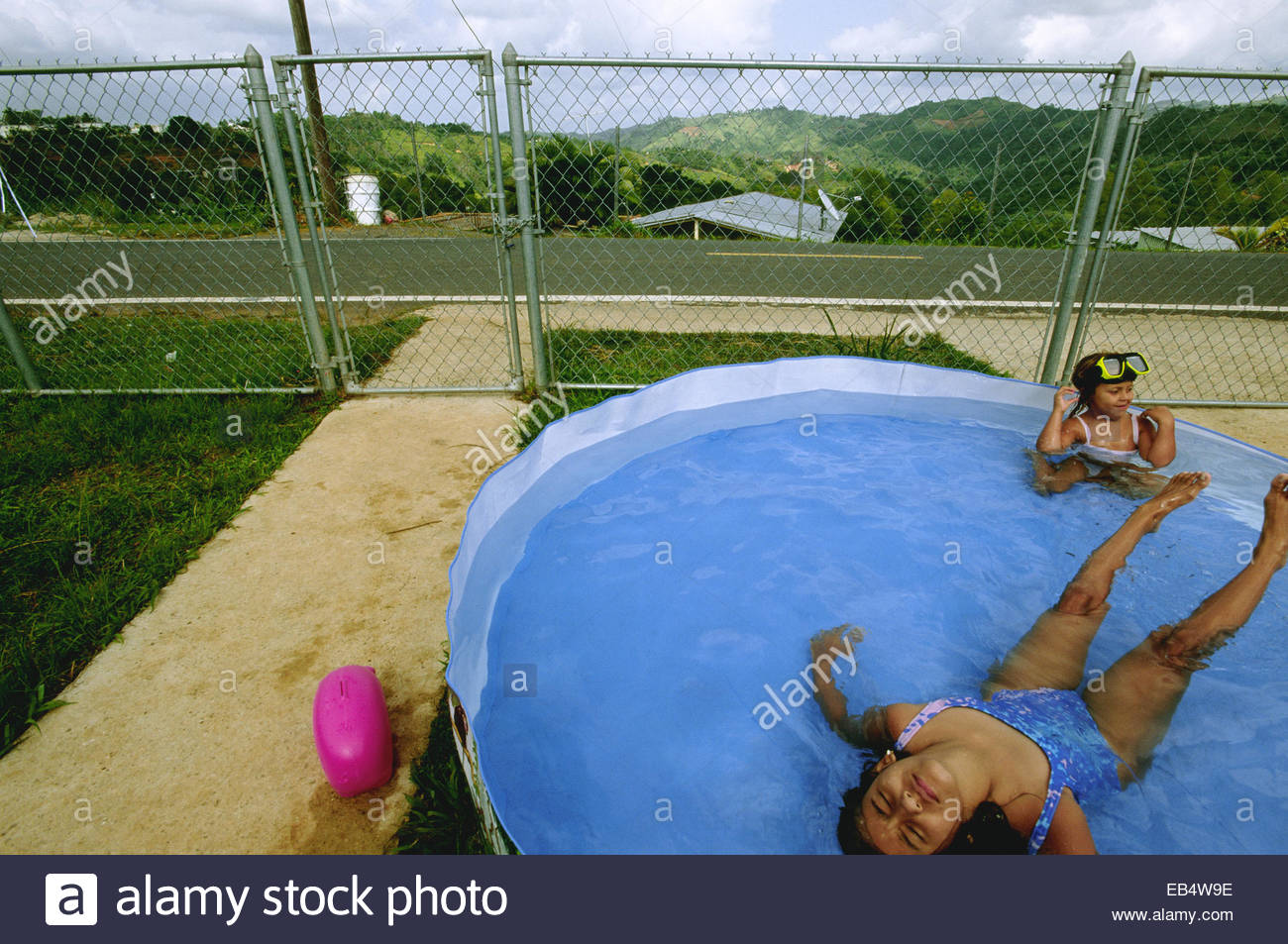Sisters keep cool in a pool in their front yard in Corozal. - Stock Image