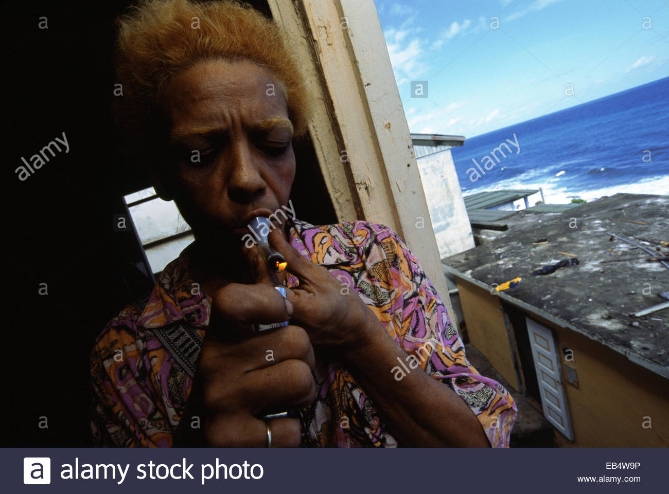 A drug addict lights up in the La Perla neighborhood of Old San Juan. - Stock Image