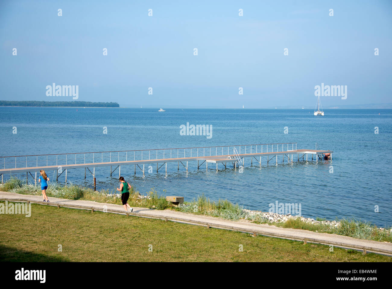 Two early morning joggers jogging along the shore of the Kattegat Sea at Ebeltoft in  East Jutland, Denmark - Stock Image