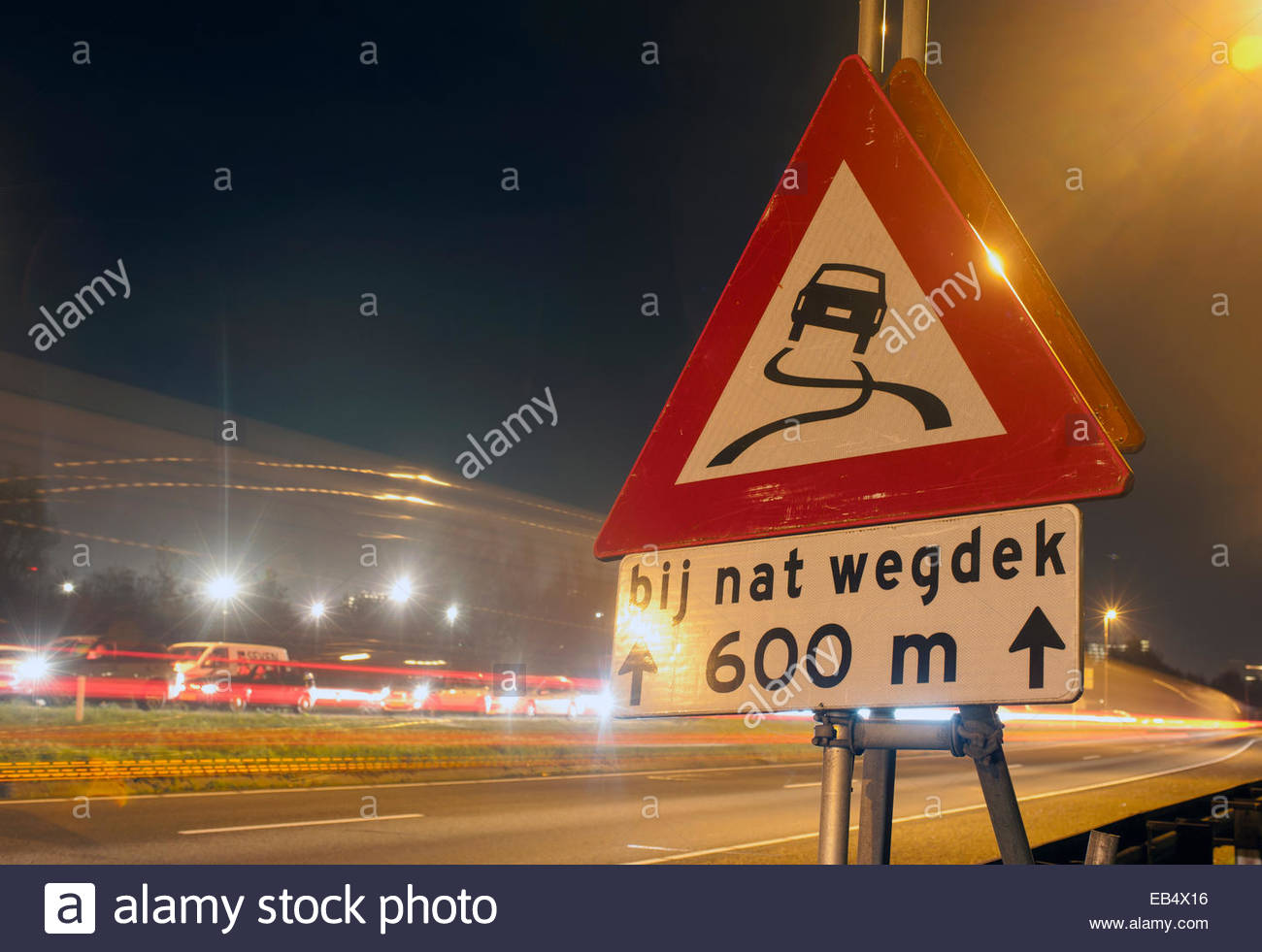 Amsterdam The Netherlands slippery when wet sign at night. Road safety. - Stock Image