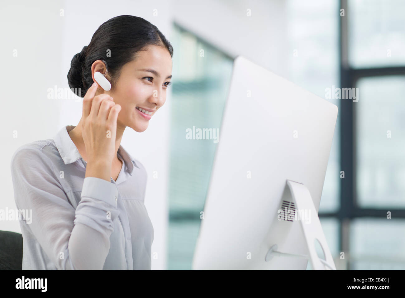 Young Businesswoman With Bluetooth Headset Working In Office Stock Photo Alamy