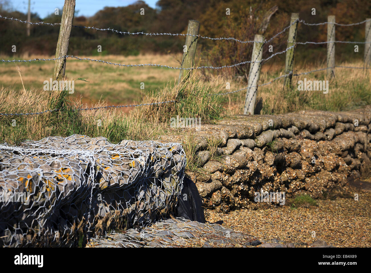 Wired stone and cement bag soil reinforcement on edge of field Stock Photo