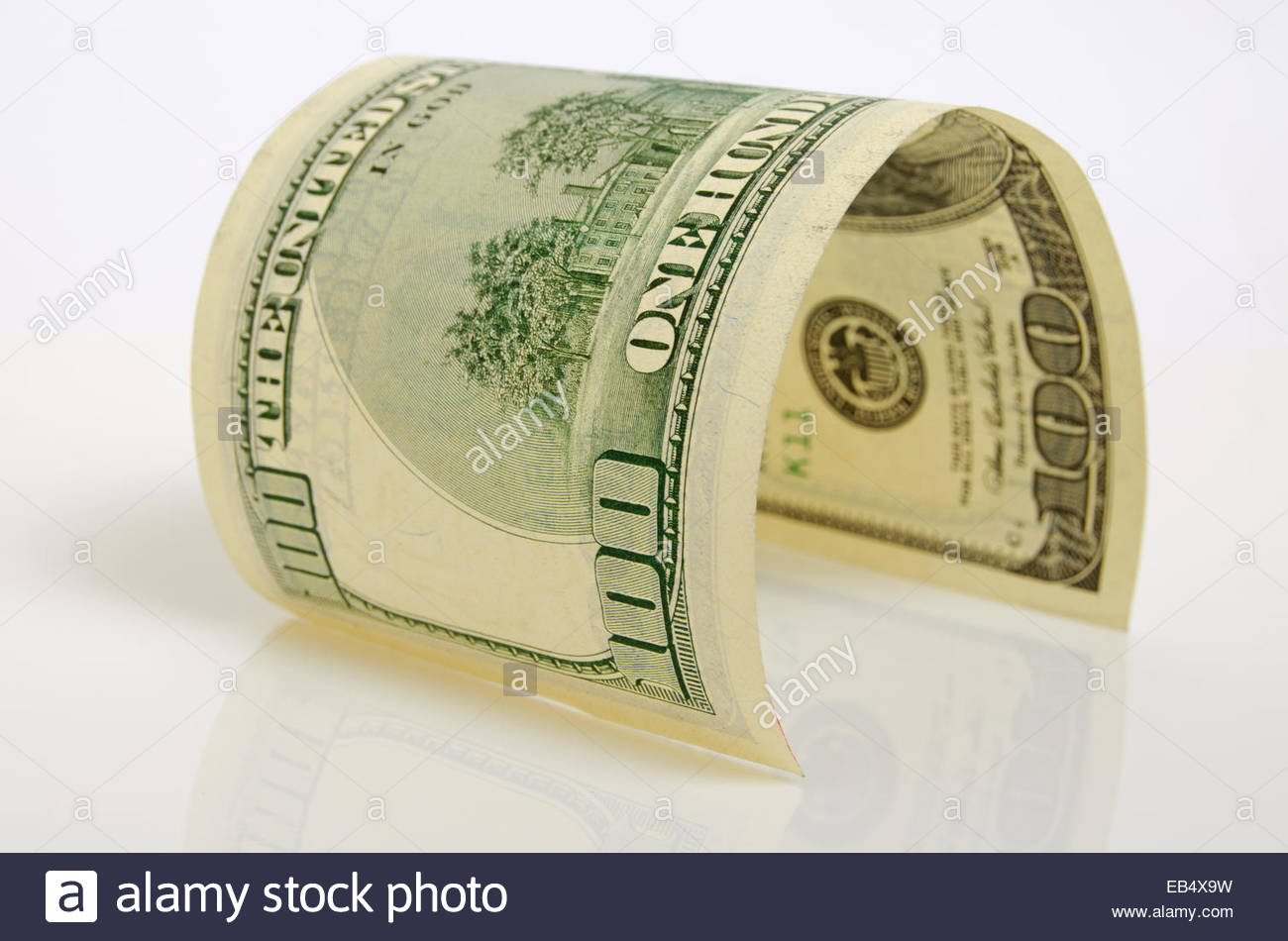 Curved hundred-dollar bill close up on a light plane. - Stock Image