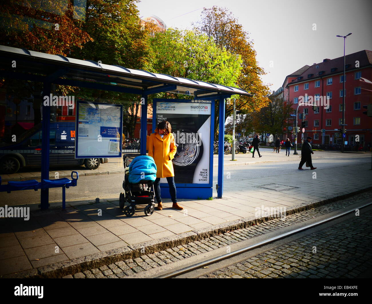 Happy Satisfy mother waiting Tram looking at baby in Kinderwagon Babywagon - Stock Image