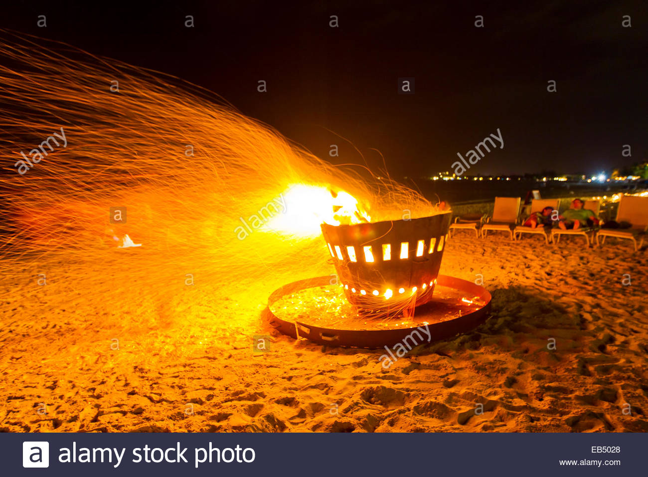 Sparks fly from a beach bonfire at the Seven Stars Resort at Grace Bay. Couples relax nearby. - Stock Image