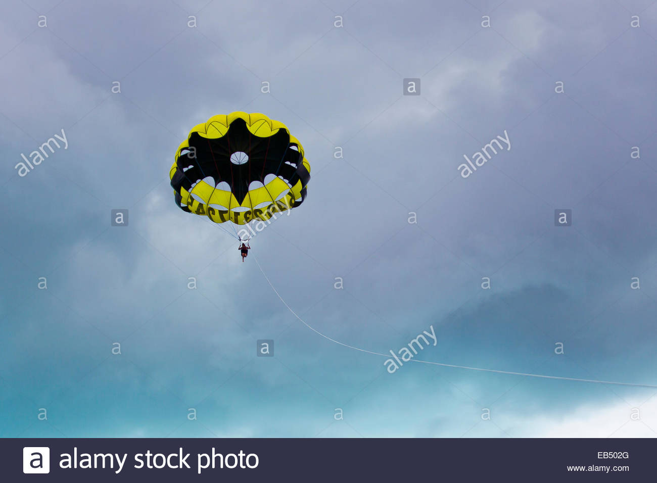 A woman parasailing over Grace Bay in a cloud-filled sky, using a Batman-themed parachute. - Stock Image
