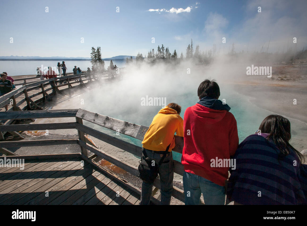 Tourists lean over a railing to observe geothermal features in a geyser basin. - Stock Image