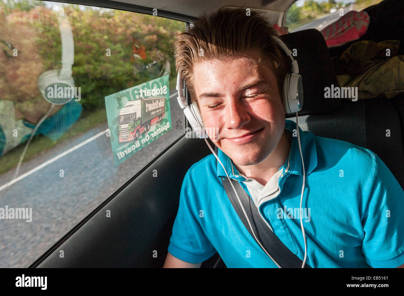 A 14 year old boy listening to music in the car Stock Photo