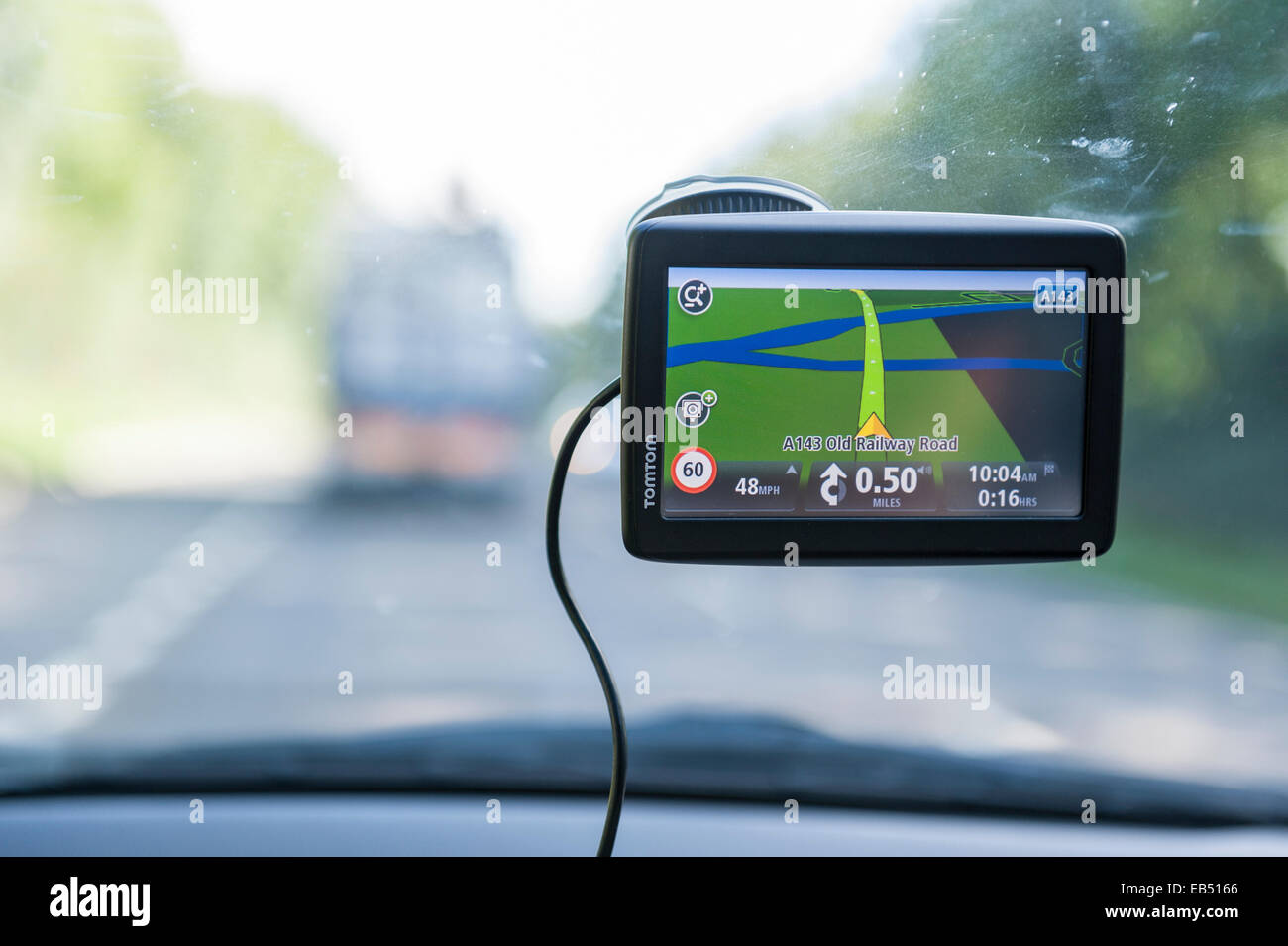 A TomTom sat nav satnav satelite navigator at work in a car - Stock Image