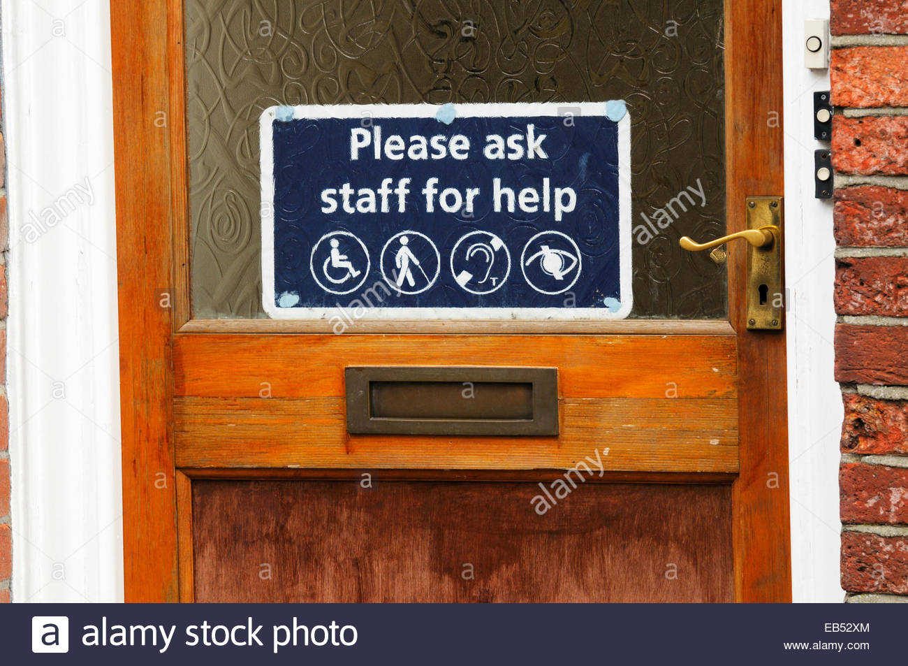 Disability sign in shop door, Blandford, Dorset, England UK - Stock Image