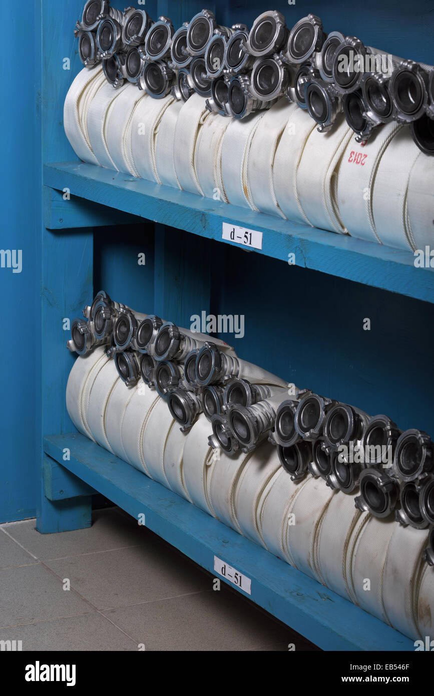 New fire hoses on a wooden shelf - Stock Image