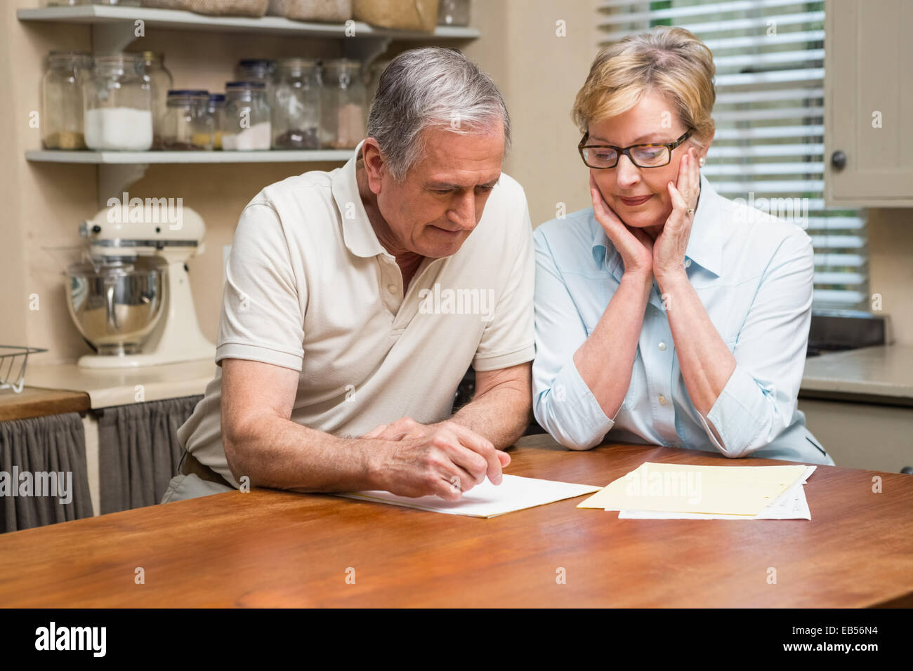 Senior couple working out their bills - Stock Image