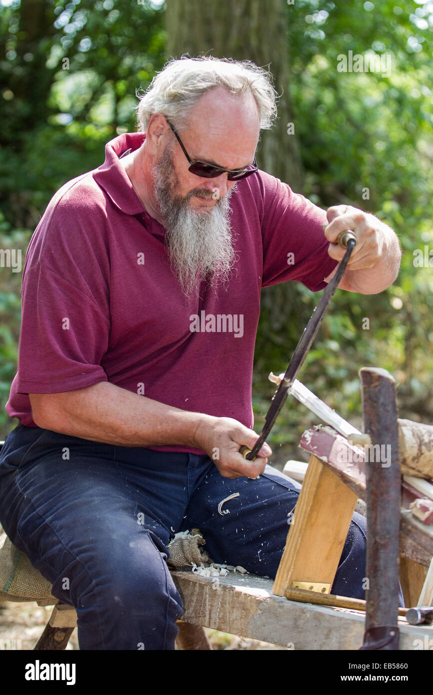 """A woodworker or """"bodger"""" uses a draw knife to prepare a wooden stave for further work in a sunny woodland glade Stock Photo"""