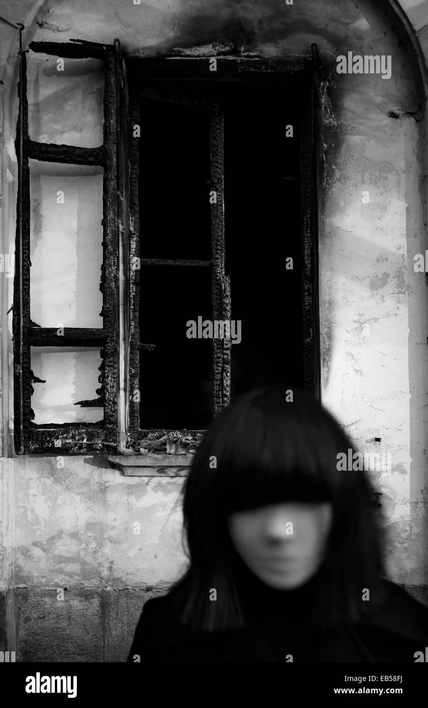 Masked girl near burned window Stock Photo