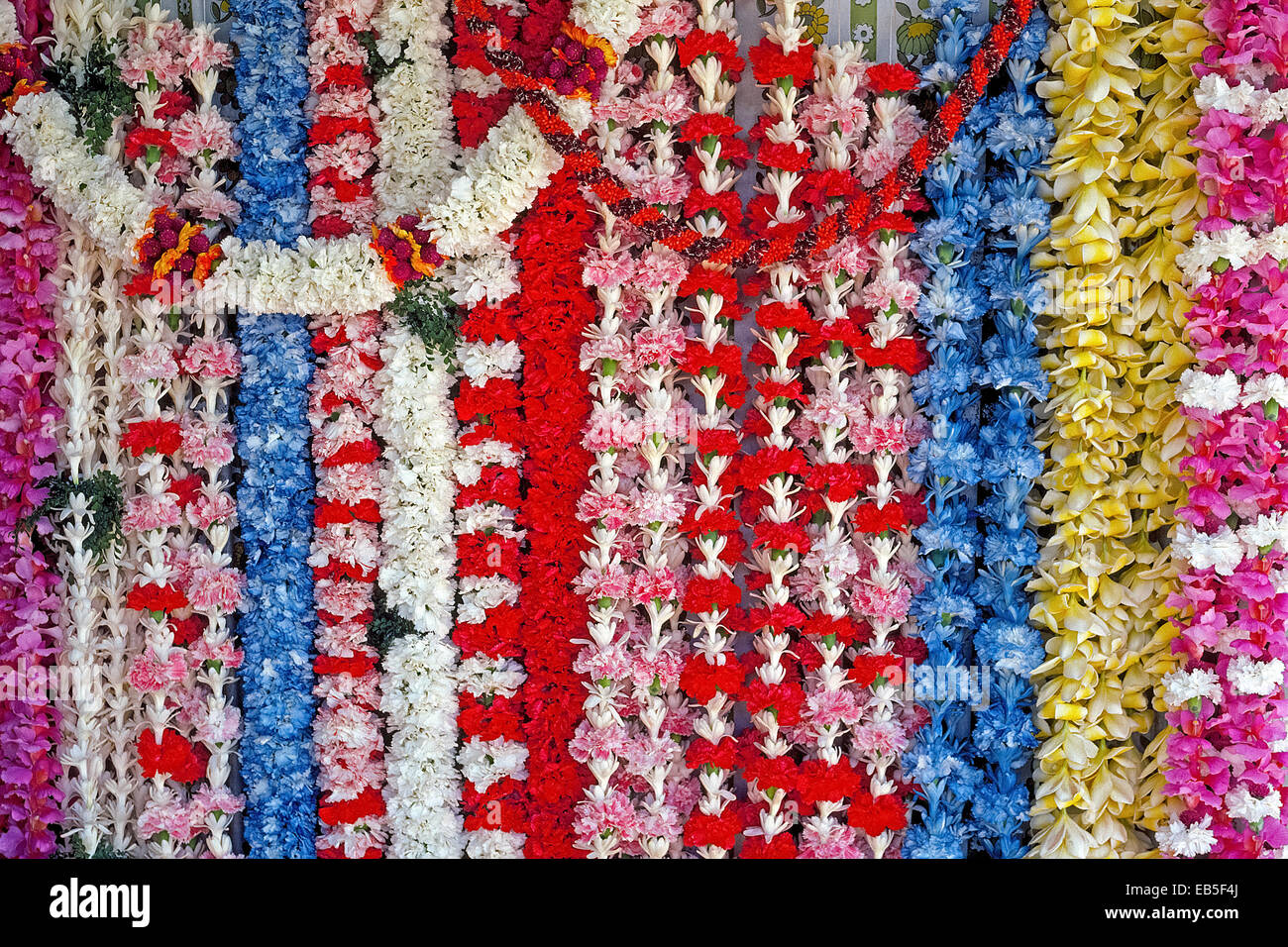 Strings of flower leis to say 'Aloha' (hello or good-bye) are for sale in lei-maker stalls at Honolulu International - Stock Image