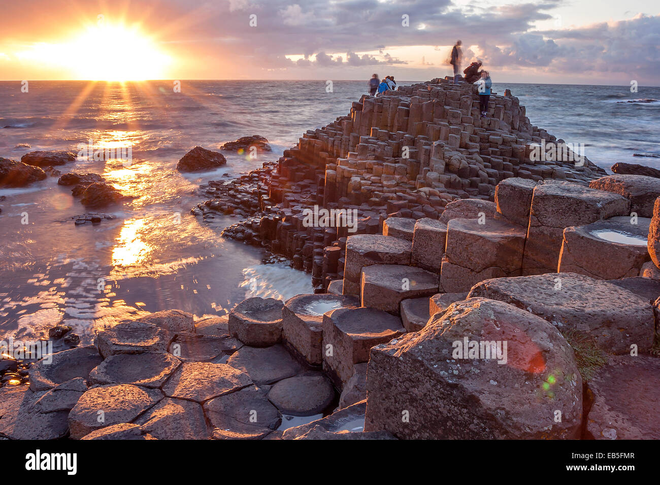 People visiting Giant s Causeway at the sunset in North Antrim, Northern Ireland - Stock Image