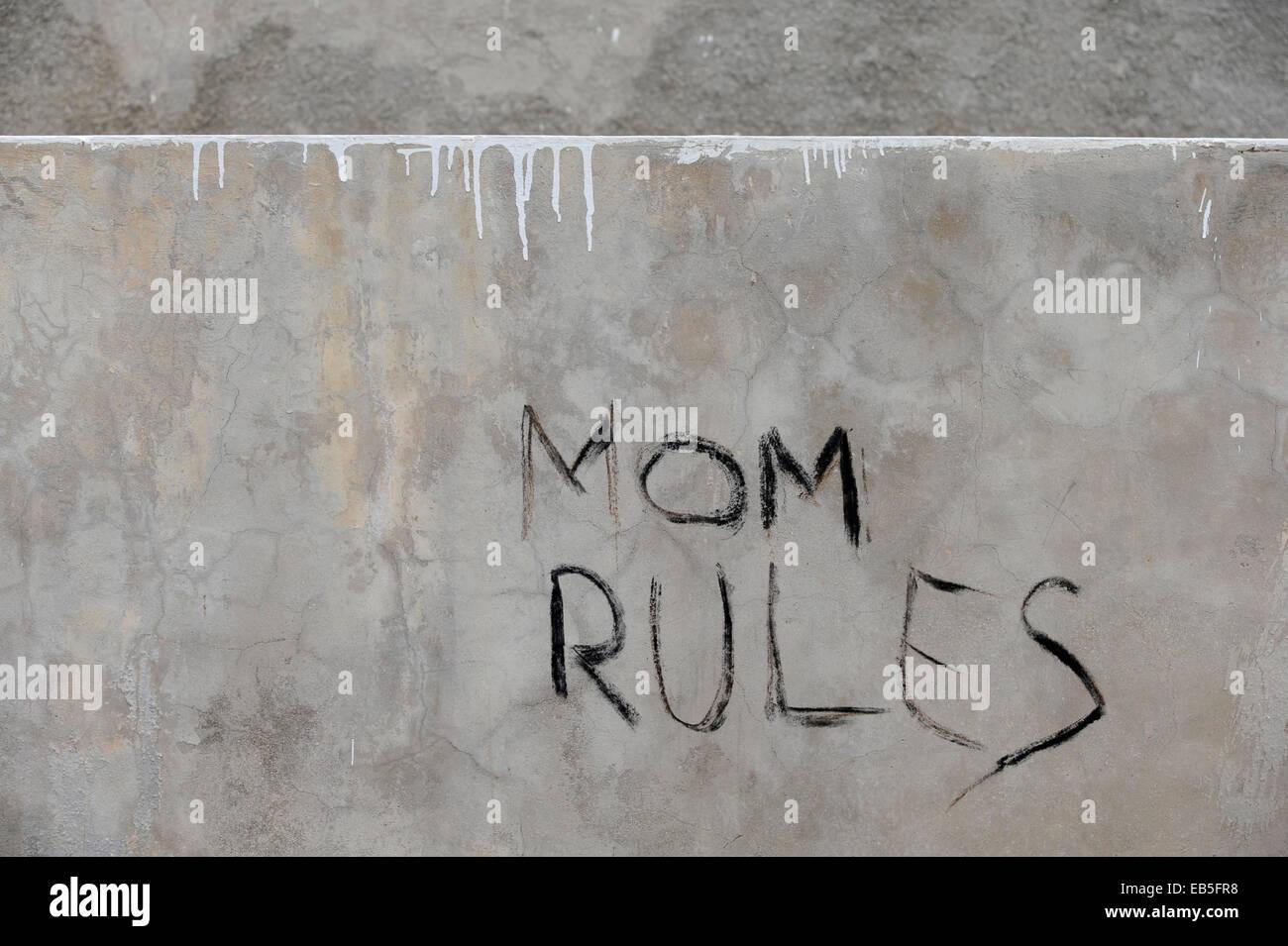 Graffiti 'Mom Rules' on grey wall - Stock Image