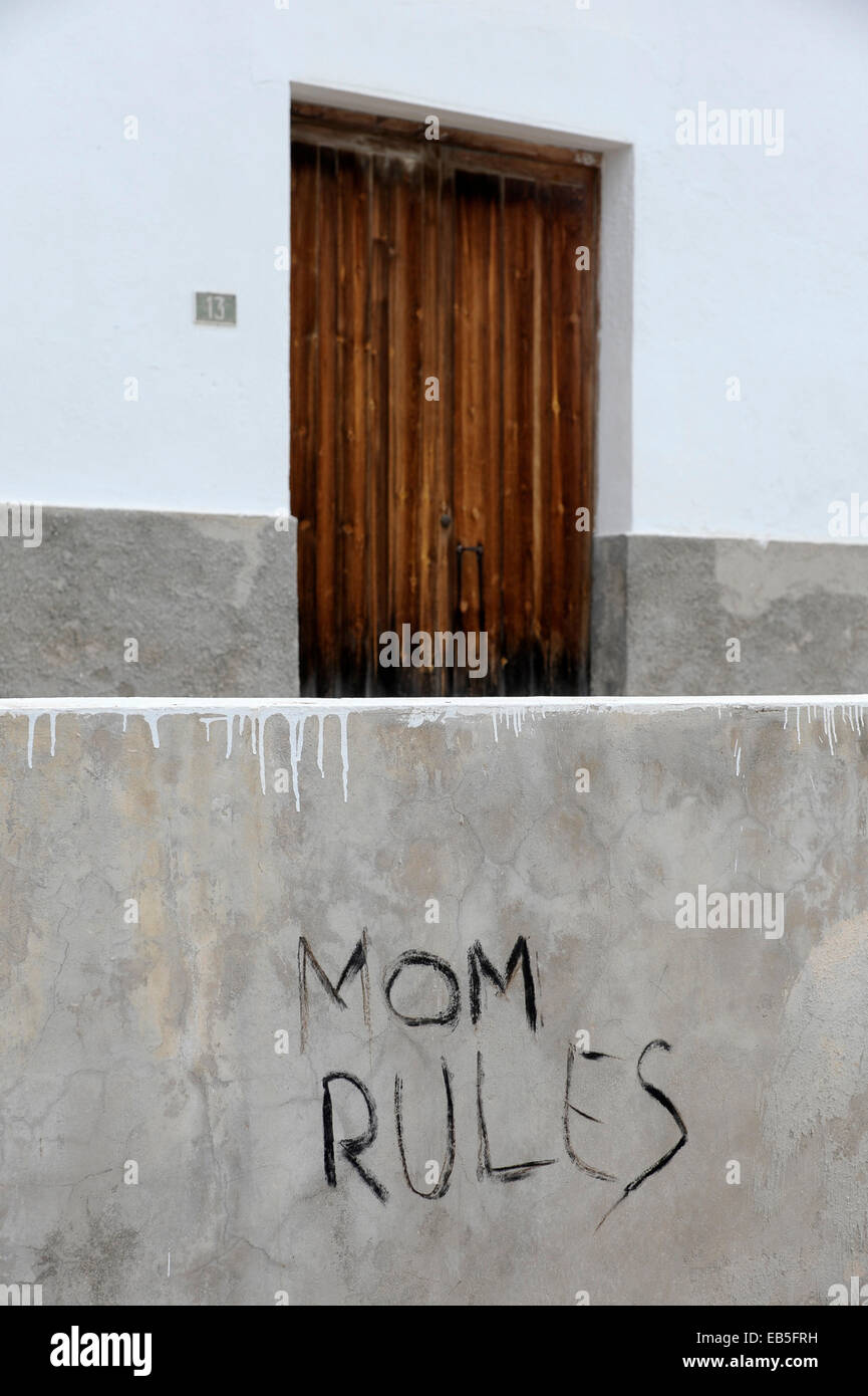 Graffiti 'Mom Rules' on gray wall in front of closed door - Stock Image
