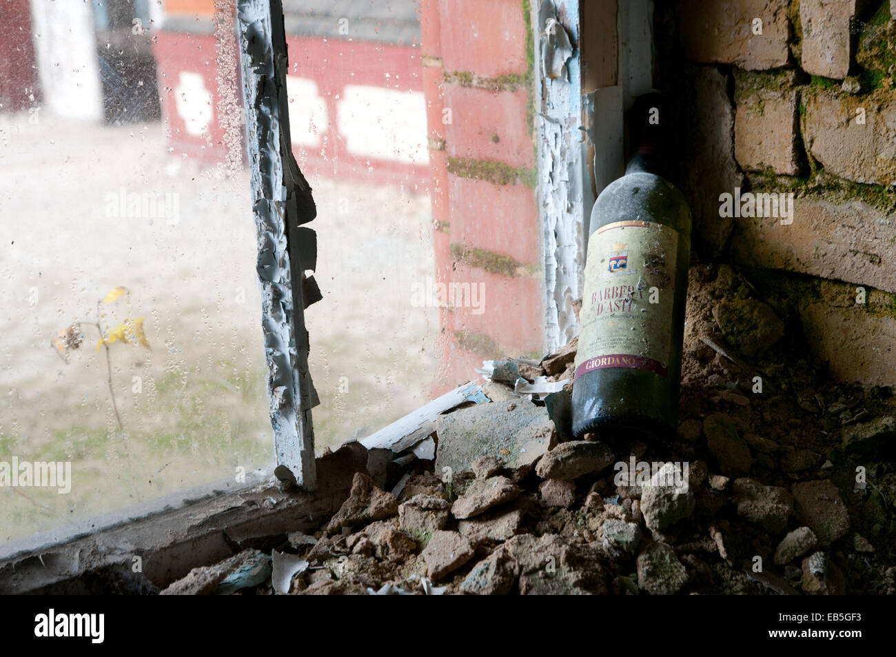 Dusty wine bottle on window sill, Beelitz Heilstaetten former TB hospital, abandoned place near Berlin - Stock Image