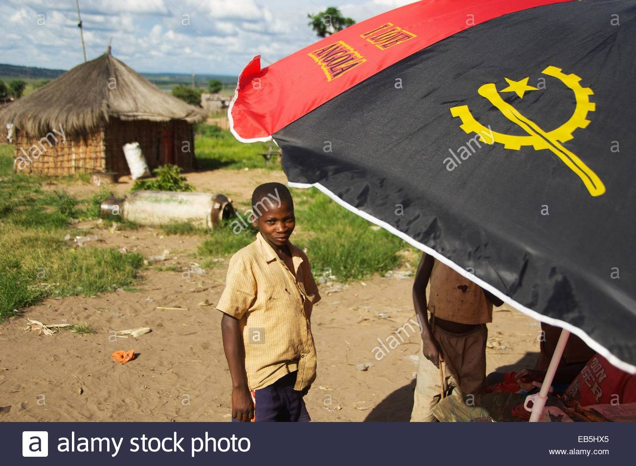The 'I love Angola' slogan on an umbrella sheltering a boys goods on his market stall in Cuito Cuanavale. - Stock Image