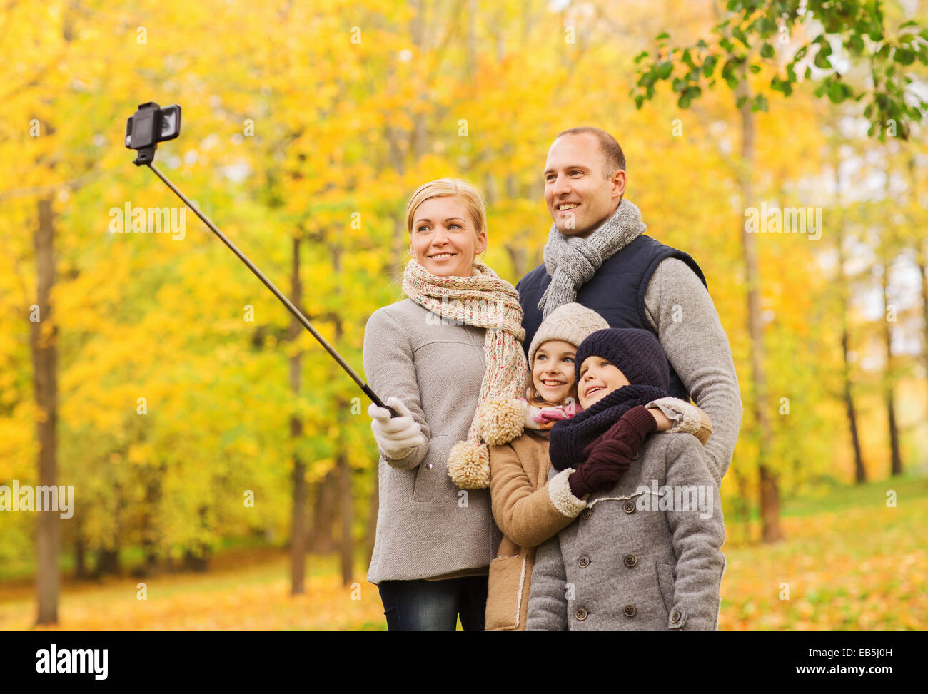 happy family with smartphone and monopod in park - Stock Image