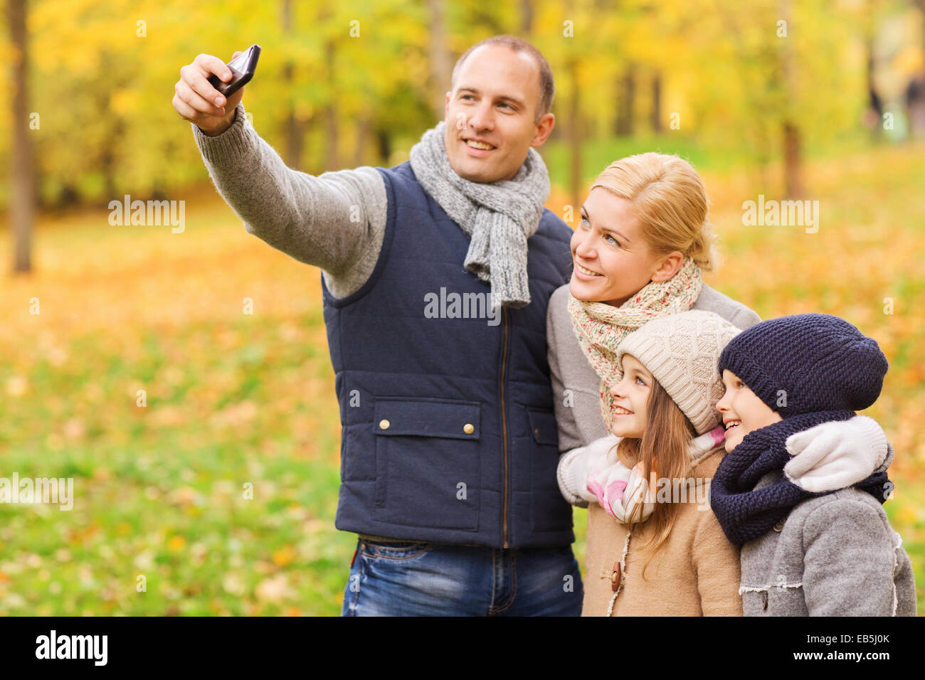 happy family with camera in autumn park - Stock Image