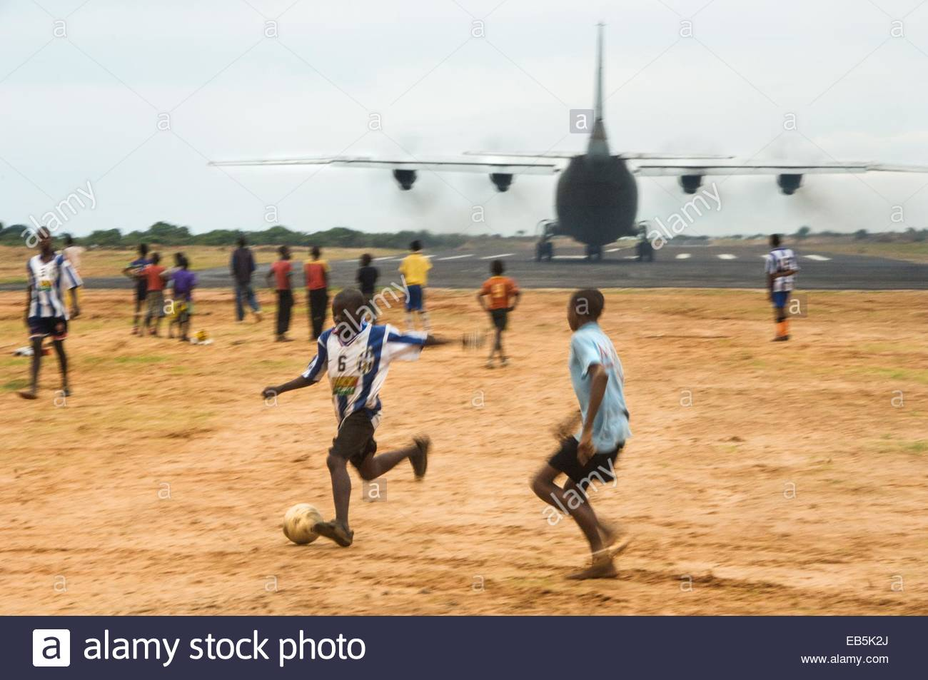 Young boys play football next to the air strip in Cuito Cuanavale. The venue played a pivotal role in the Angolan - Stock Image