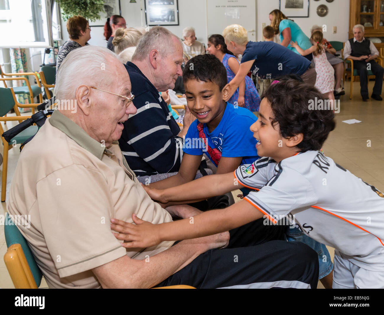 Two six-year-old boys from a kindergarten group seek contact to a ninety-year-old senior in a retirement home - Stock Image