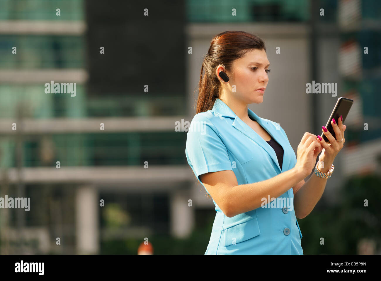 Adult hispanic person with mobile phone and wireless bluetooth headset, talking on telephone in the street out office - Stock Image