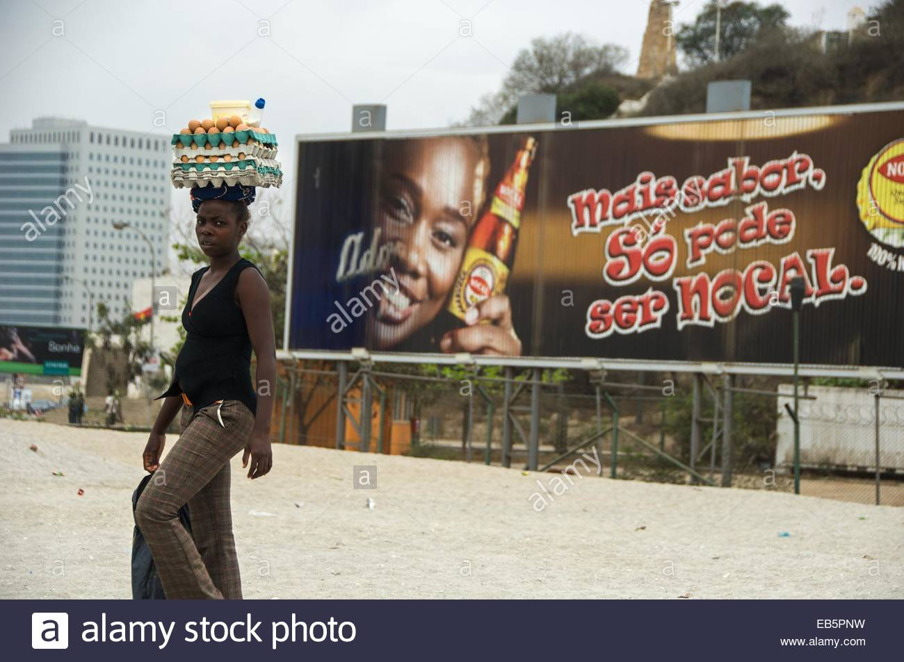 A woman dressed in tartan trousers carries milk, butter and eggs on her head while walking through the city of Luanda. - Stock Image