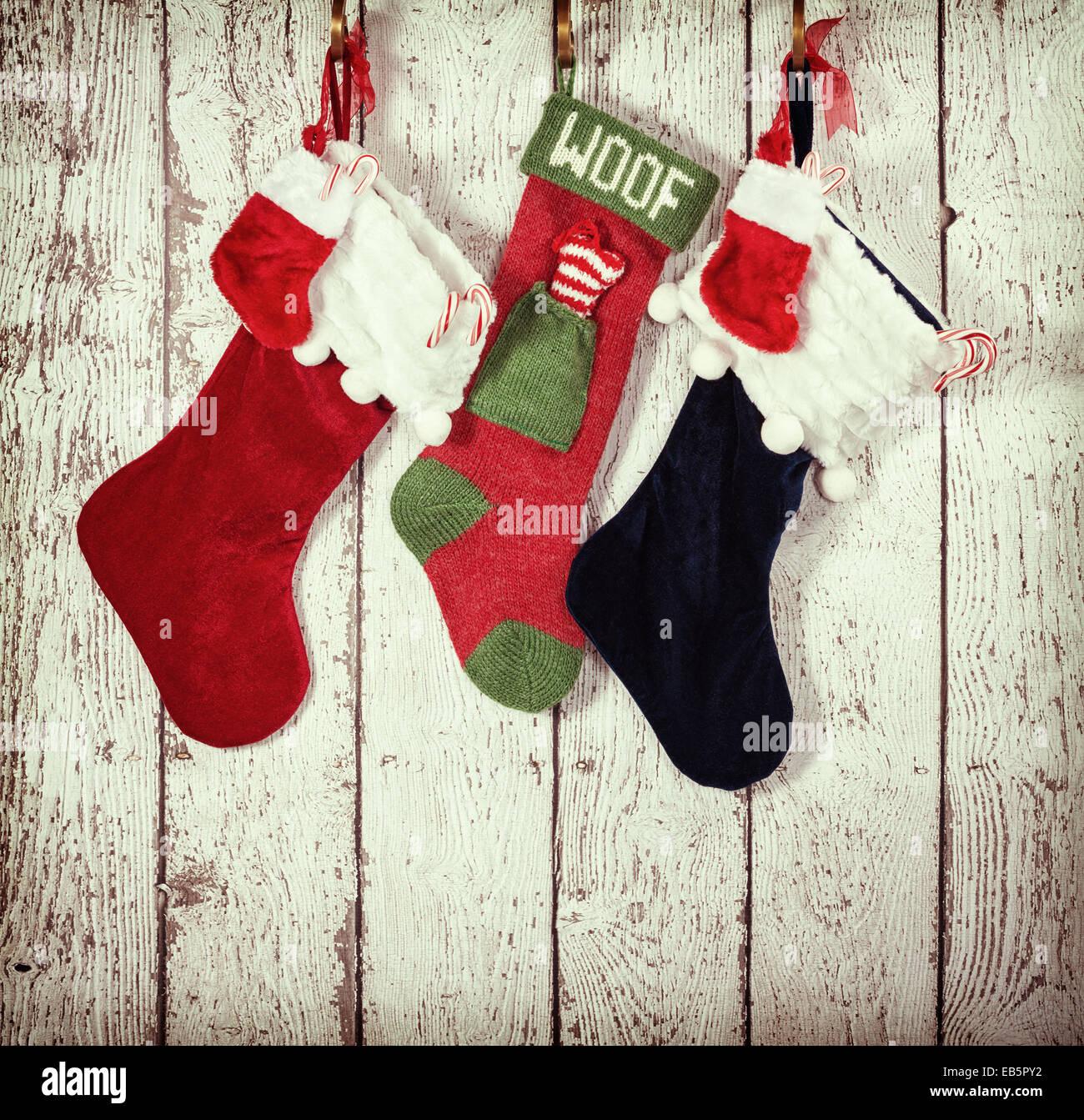 Christmas stocking hanging against rustic wood background - Stock Image