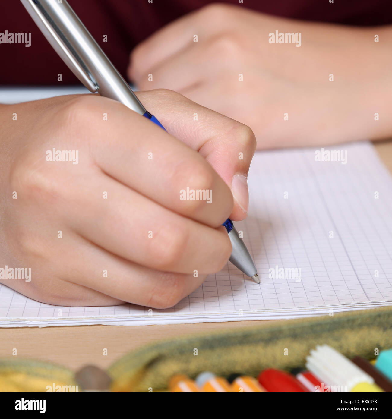 Young student writing with hand in his exercise book at school - Stock Image