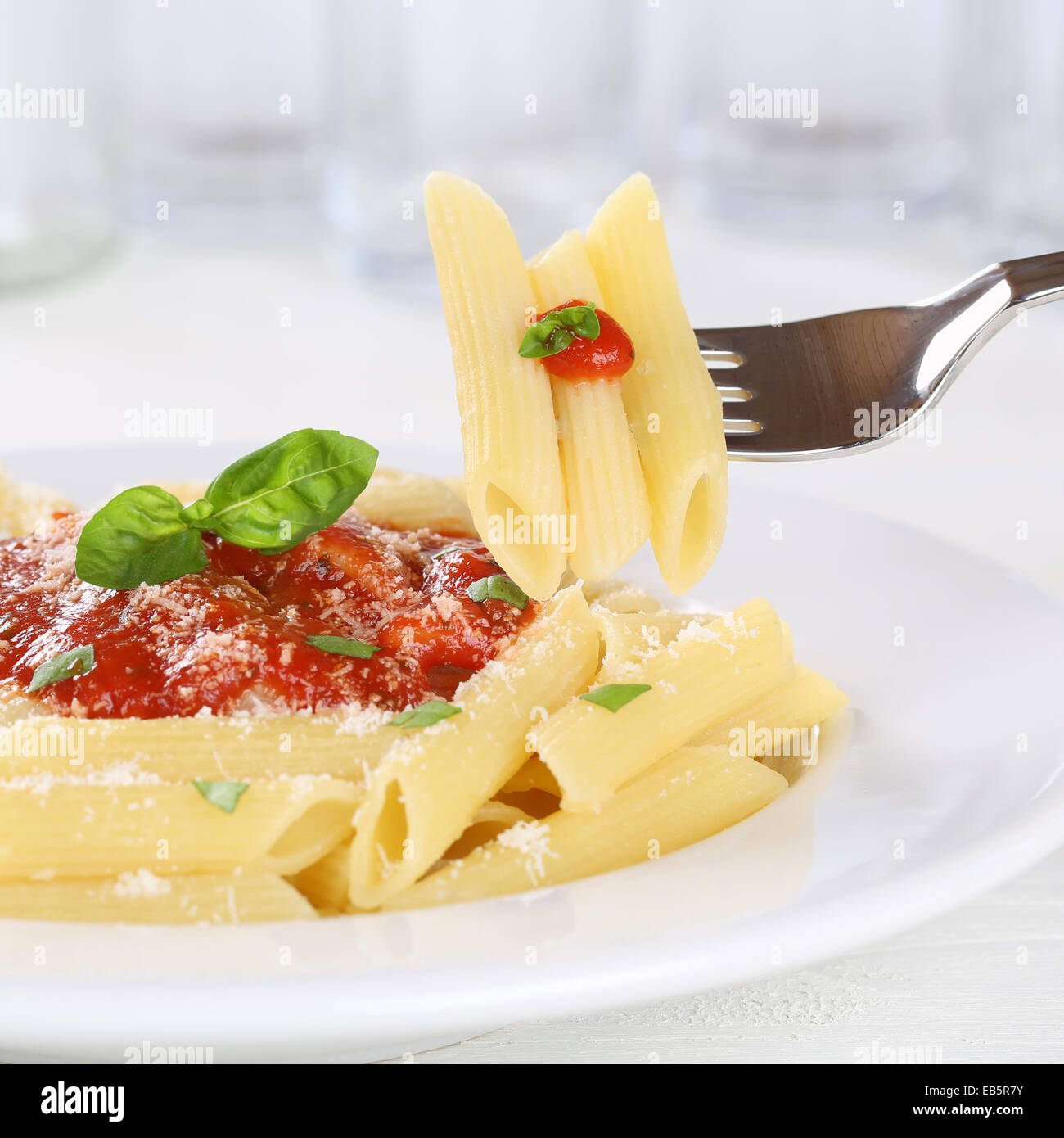 Eating pasta Rigate Napoli with tomato sauce with fork on a plate - Stock Image