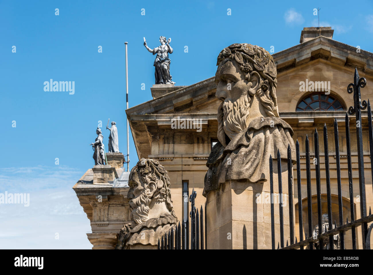 Grotesque decorative stone figure heads outside the Sheldonian Theatre, behind which is seen the Muses on the Clarendon Stock Photo