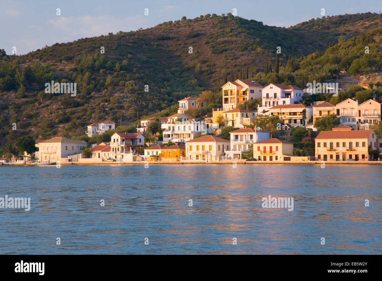Vathy, Ithaca, Ionian Islands, Greece. View across the harbour to modern houses lit by the setting sun. - Stock Image