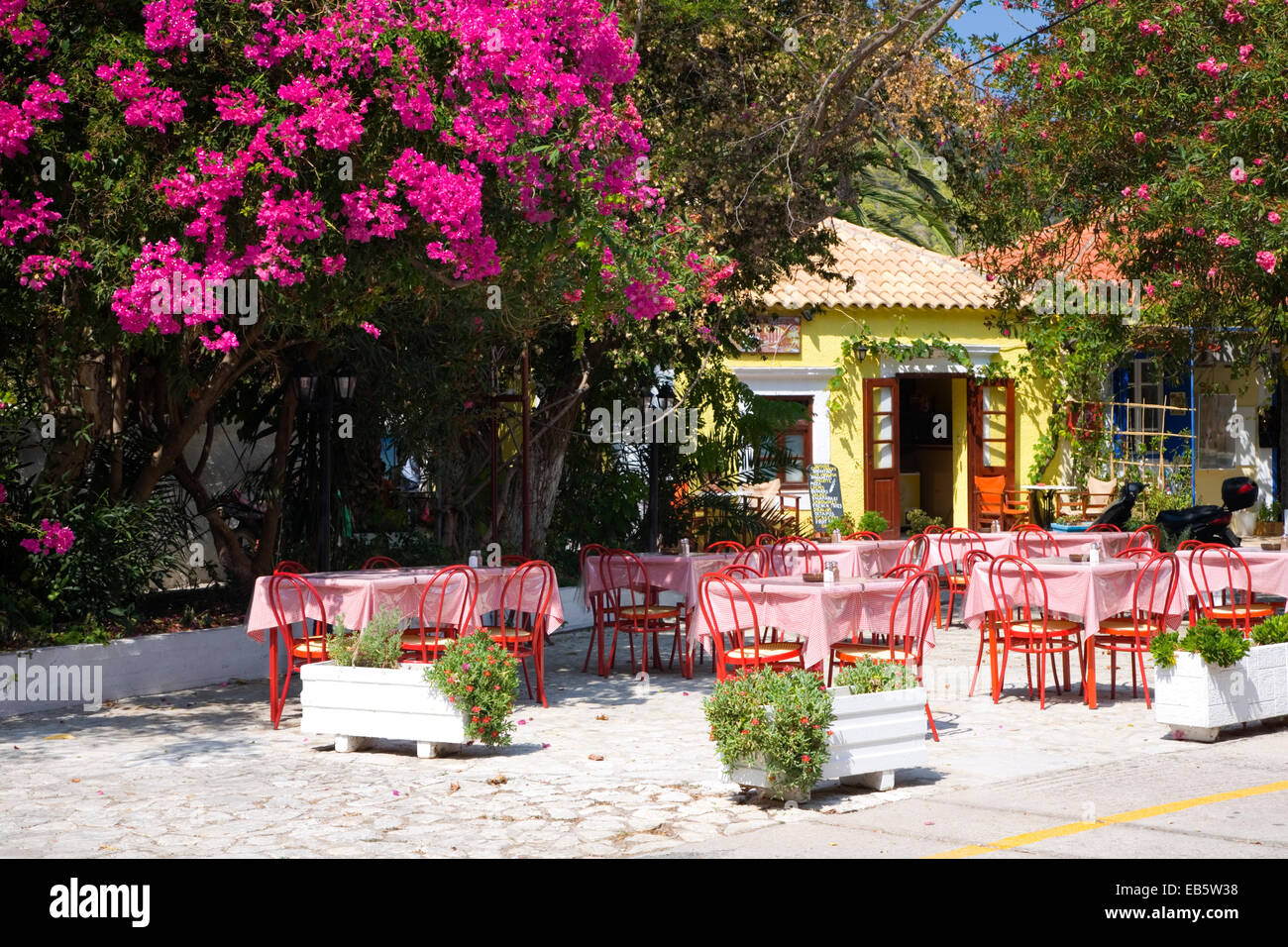 Asos, Kefalonia, Ionian Islands, Greece. Colourful taverna in the village square, bougainvillea prominent. - Stock Image