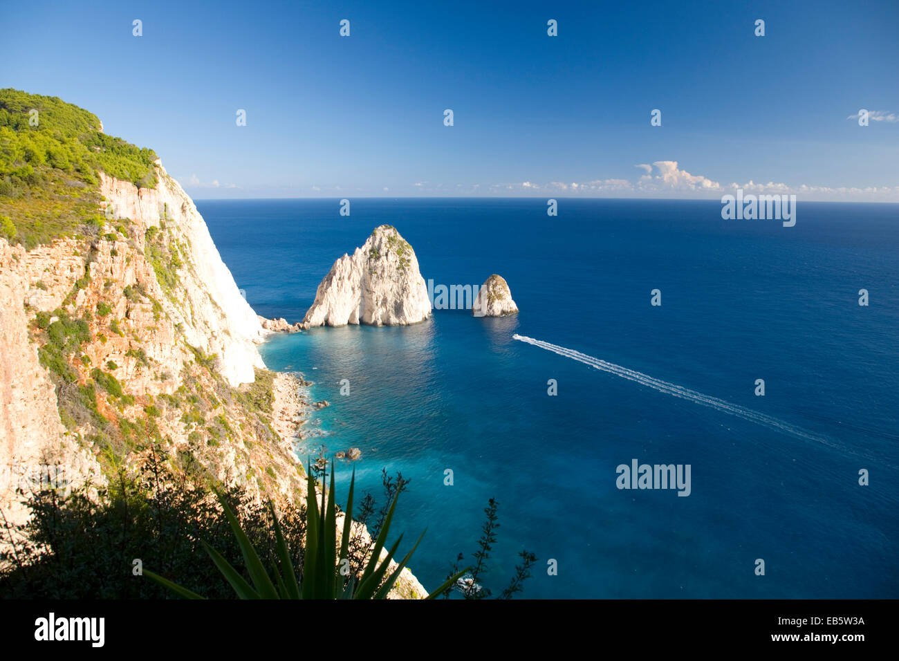 Keri, Zakynthos, Ionian Islands, Greece. View to the Myzithres Rocks from clifftop at Cape Keri, boat speeding across - Stock Image