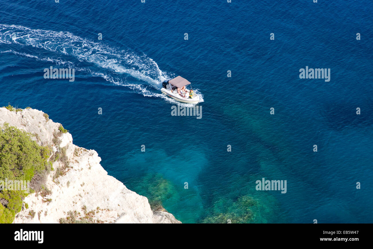 Korithi, Zakynthos, Ionian Islands, Greece. Small boat passing beneath cliffs above the Blue Caves at Cape Skinari. - Stock Image