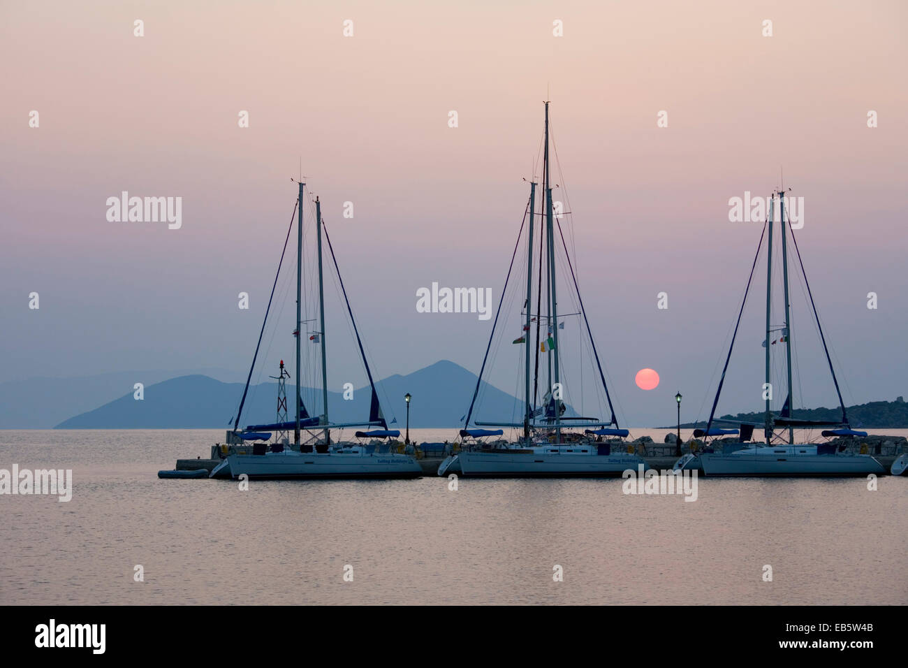 Frikes, Ithaca, Ionian Islands, Greece. View across the harbour at sunrise, the distant island of Atokos visible. - Stock Image
