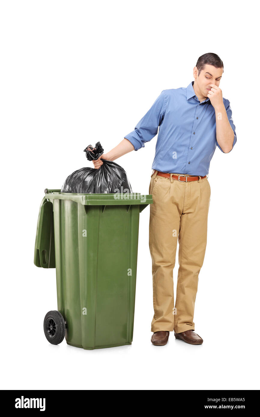 Full length portrait of a man throwing out a stinky bag of trash isolated on white background - Stock Image