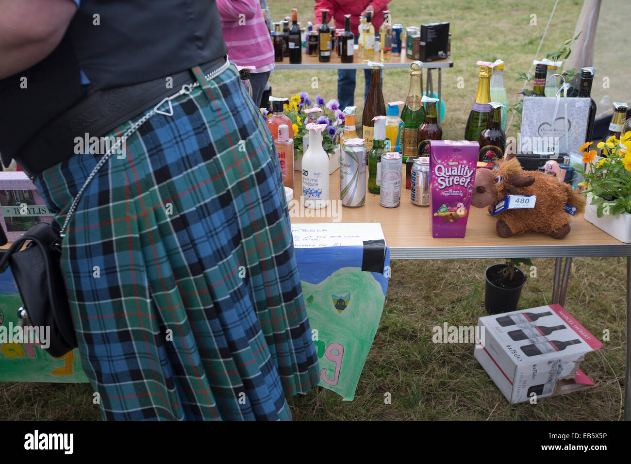 A man in a Scottish kilt walking past a stall with raffle prizes at the Dalmally Agricultural Society Show, Dalmally, - Stock Image