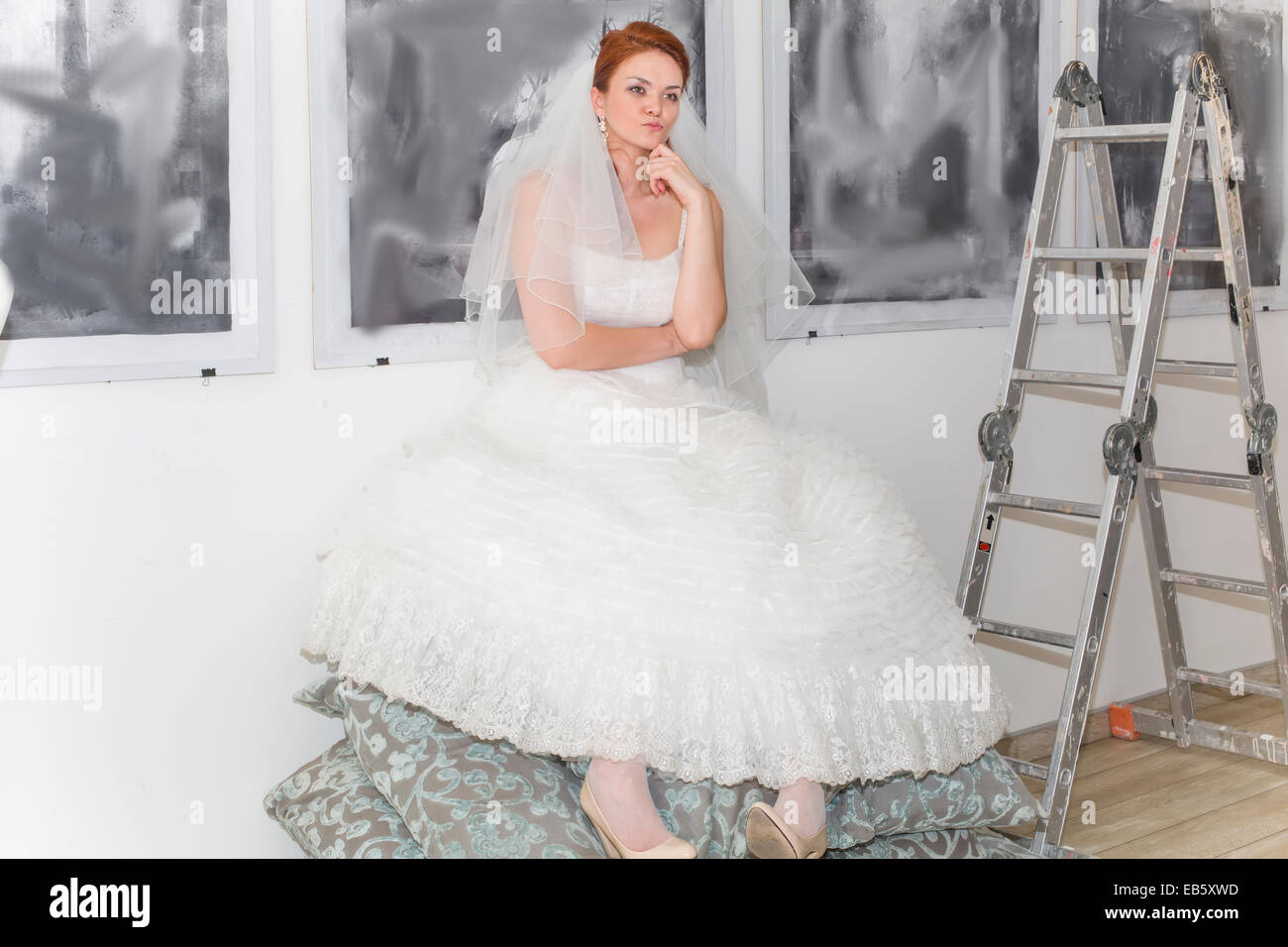 Bride in the artist sat on pillows and lost in thought - Stock Image