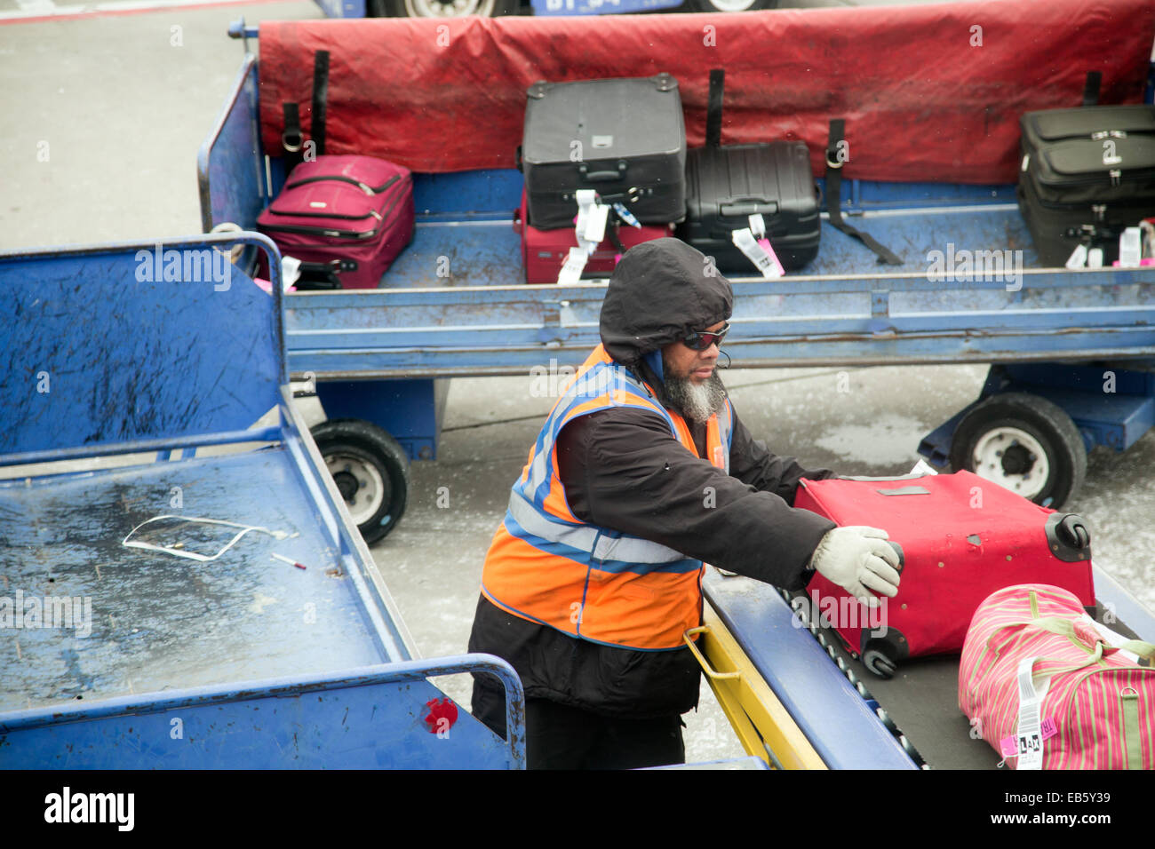 Denver, Colorado - A baggage handler unloads luggage from a Southwest Airlines plane at Denver International Airport. - Stock Image