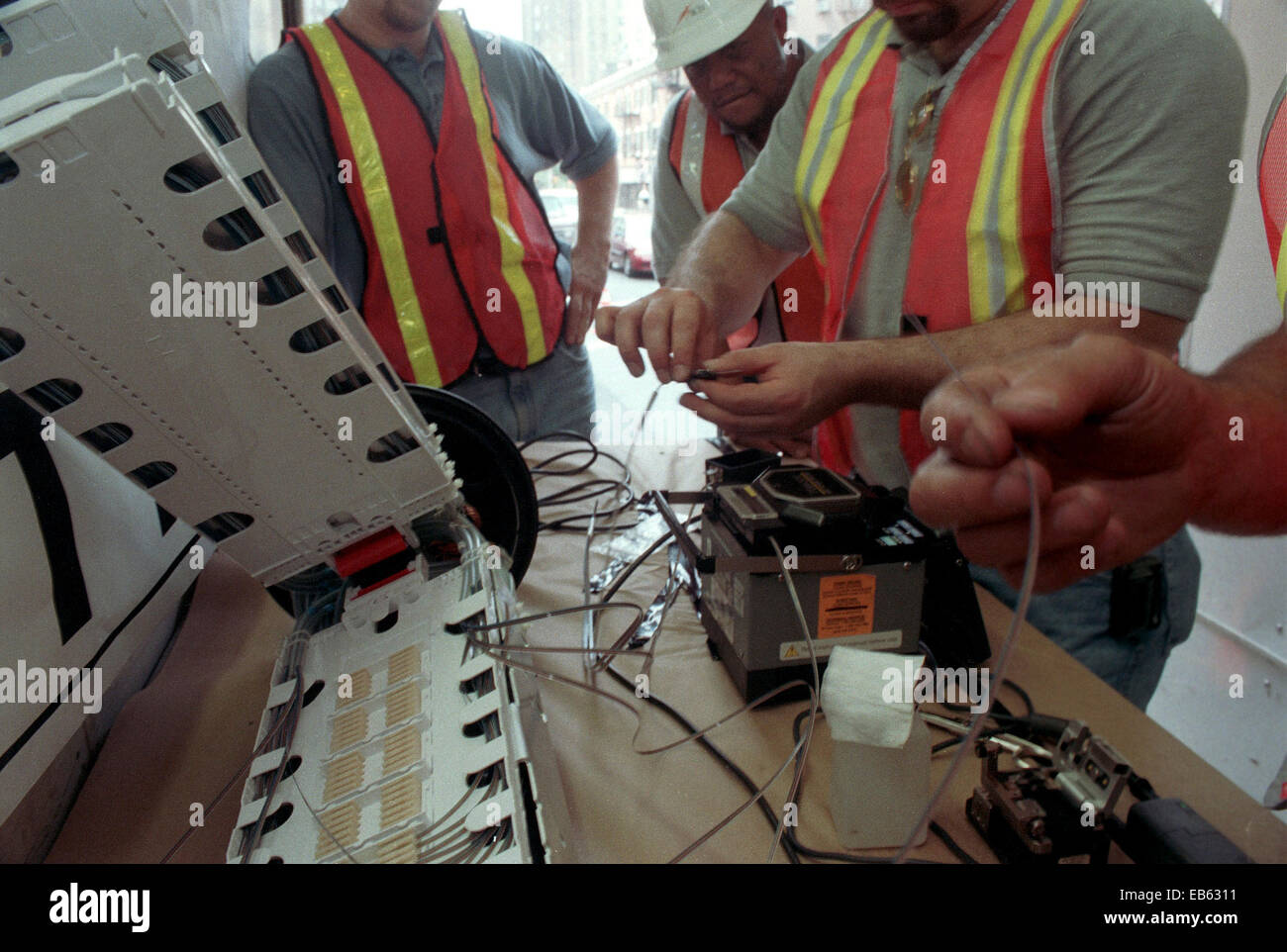Fiber Optic Cable Splicing : Workers splice fiber optic cables in a mobile